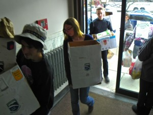 Champlain College students deliver boxes of food they collected in a food drive to the Newport Food Shelf.