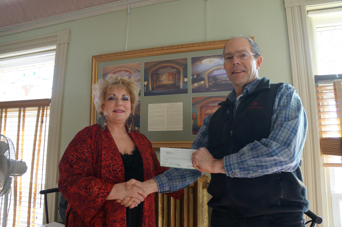 Haskell Opera House Director, Lynn Leimer is presented with a $3,000 Check from Plum Creek, by Community Affairs Manager, Mark Doty to assist with the Phase III Technological Upgrade at the Opera House.