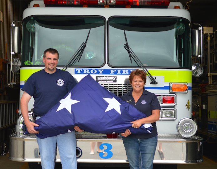 Troy Fire Department Chief and North East International Mutual Aid (NEIMA) member Bobby Jacobs accepting a new U.S. Flag from Community National Bank Vice President Cindy LaGue.